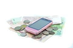 Mobiltelefon och pengar Fotografering för Bildbyråer