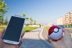Mobiltelefon och pokeball för man hållande Royaltyfria Bilder