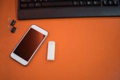 Mobiltelefon och radergummi och tangentbord på trätabellen av apelsinen arkivbild