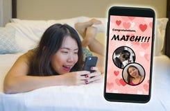 Mobiltelefon och ung härlig och lycklig asiatisk kinesisk flicka som använder den gladlynta online-datera appen motta en match me royaltyfri foto