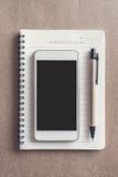 Mobiltelefon på anteckningsboken på skrivbordkontor med kopieringsutrymme Arkivbilder