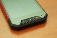 Mobiltelefon på en trätabell Royaltyfria Foton
