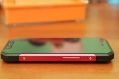 Mobiltelefon på en trätabell Fotografering för Bildbyråer