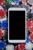Mobiltelefon på mångfärgade kasinochiper Royaltyfria Bilder