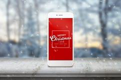 Mobiltelefon på skrivbordet med massage för glad jul Arkivbilder