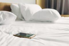 Mobiltelefon på vit säng på morgonen arkivfoton