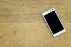Mobiltelefon på wood bakgrund Arkivbild