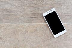 Mobiltelefon på wood bakgrund Royaltyfria Foton