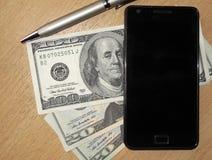 Mobiltelefon, pengar och penna Royaltyfri Foto