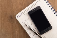 Mobiltelefon, penna och dagordning royaltyfria bilder