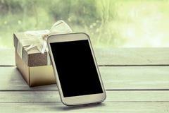Mobiltelefon smart telefon, telefon med gåvaasken på trätabellen Royaltyfri Bild