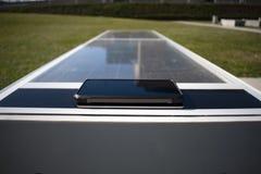 Mobiltelefon som avlägset laddar på en sol- bänk arkivbilder