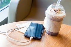 Mobiltelefon som laddar i kafét med en plast- kopp av med is chokladfrappe fotografering för bildbyråer