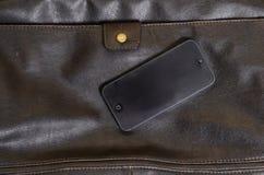 Mobiltelefon som ligger på en läderpåse Royaltyfri Fotografi