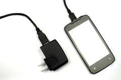 Mobiltelefon und Ladegerät auf weißem Hintergrund Stockfotografie