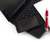 Mobiltelefon und Notizblock auf Laptop Stockfotografie