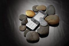 Mobiltelefon und Steine stockfotografie