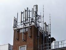 Mobiltelefonantennae överst av byggnad arkivfoton