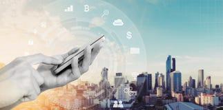 Mobiltelefonapplikation och teknologi Räcka genom att använda mobilen smart telefon- och stadssoluppgångbakgrund royaltyfri bild