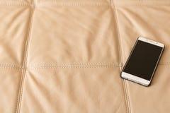 Mobiltelefonen är på lädersoffan royaltyfria bilder