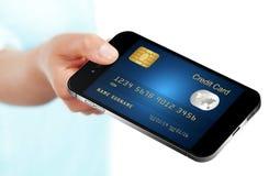 Mobiltelefonen med kreditkorten holded vid handen som isolerades över vit Arkivfoto