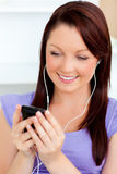 mobiltelefonen som charmar henne, lyssnar musik till att använda kvinnan Royaltyfri Bild