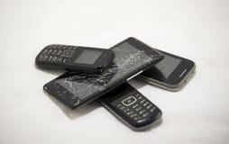 Mobiltelefoner gammalt som är brutna på en vit bakgrund royaltyfria bilder