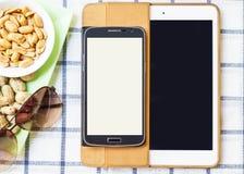 Mobiltelefoner och minnestavlor på en vit bakgrund Fotografering för Bildbyråer