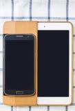 Mobiltelefoner och minnestavlor på en vit bakgrund Royaltyfri Foto