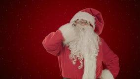mobiltelefonframsidan hans isolerade look santa förvånade talande white på röd bakgrund med snö Arkivfoton