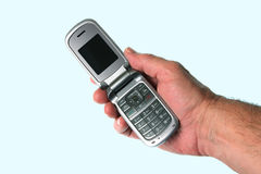 Moblie (Cell) Phone in Hand. A mans hand holding a mobile (cell) flip phone Royalty Free Stock Photography