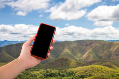 Moblie phone on hand with nature background Stock Photo