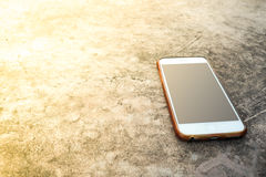 Moblie smart phone on stone table sun light background. Royalty Free Stock Photography
