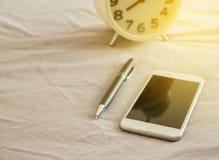 Moblie, smartphonepen ane alarmclock op bed in ochtend Royalty-vrije Stock Foto's