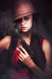 Mobster Toting A Gun. Sexy woman mobster with her hat pulled low over her eyes toting a large handgun in a dark shadowed portrait of criminal underworld figure Royalty Free Stock Photos
