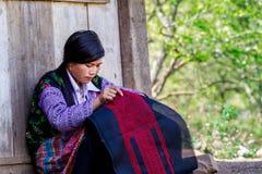 MOC CHAU PLATEAU, VIETNAM - FEBRUARY 5, 2014 - An unidentified ethnic woman lacing scarves Stock Photos