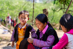 MOC CHAU PLATEAU, VIETNAM - FEBRUARY 5, 2014 - An unidentified ethnic woman lacing scarves Royalty Free Stock Photo