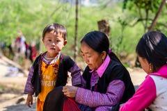 MOC CHAU PLATEAU, VIETNAM - FEBRUARY 5, 2014 - An unidentified ethnic woman lacing scarves Royalty Free Stock Photo