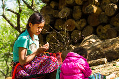 MOC CHAU PLATEAU, VIETNAM - FEBRUARY 5, 2014 - An unidentified ethnic woman lacing scarves in a plum plantation. Royalty Free Stock Images