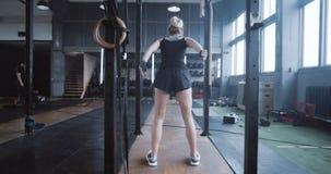 Moc i motywacja, kamera podąża za młodą blondynką sportową skaczącą do przodu, szkoląc się w zwolnionym tempie na sali gimnastycz zbiory wideo