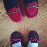 Moccasin Girls. A mother and daughter's feet in moccasins against a wood floor Royalty Free Stock Photography