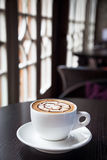 Mocha coffee drink on a wood table by the window Royalty Free Stock Images