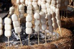 Mochi-Nachtisch in der hölzernen Stockaufsteckspindel auf dem Stroh setzte sich in einen Kreis um die Asche für das Rösten stockbild