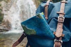 Mochila azul del inconformista, y primer del mapa Visión desde el fondo de la cascada de Front Tourist Traveler Bag On Aventura d Foto de archivo