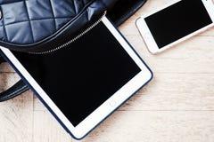 Mochila con un teléfono de la tableta Fotos de archivo