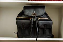 Mochila de cuero negra con los bolsillos con cremallera de oro en un estante blanco en la tienda imagen de archivo