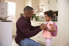 Mochila de Helps Daughter With del padre como ella se va para la escuela imagen de archivo libre de regalías