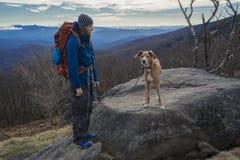 Mochila del hombre y del perro que camina en montañas Foto de archivo