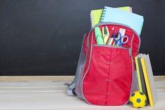 A mochila do saco de escola fornece o fundo de madeira do quadro-negro imagem de stock royalty free