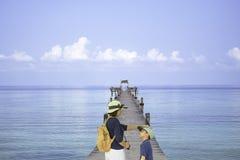Mochila e hijo del hombro de la madre que caminan en el barco del embarcadero del puente de madera en el mar y el cielo brillante imagenes de archivo